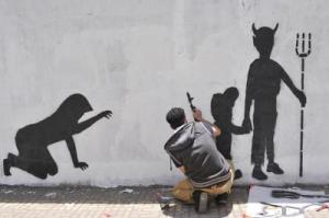 Sanaa, attivista realizza graffito contro il reclutamento di bambini soldato (foto Xinhua) Adnkronos.com