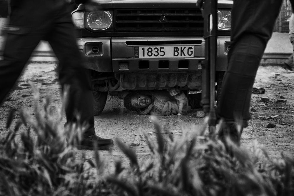 Un migrante sfugge ai controlli nascondendosi sotto una macchina. Foto presa da worldpressphoto.org. Foto di Gianfranco Tripodo, third prize singles in General News at World Press Photo Contest 2015