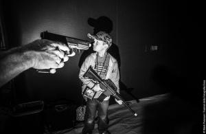 ©Mark Peterson. Un bambino tiene in mano un fucile giocattolo. Al suo fianco un adulto